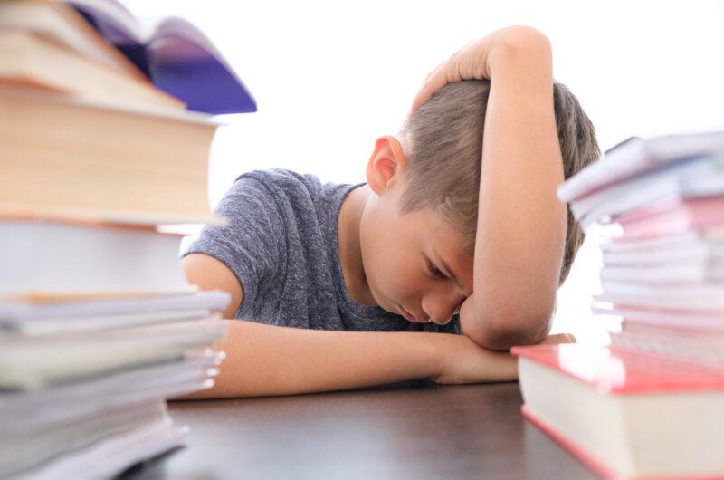 Criança aparentemente cansada em meio aos livros