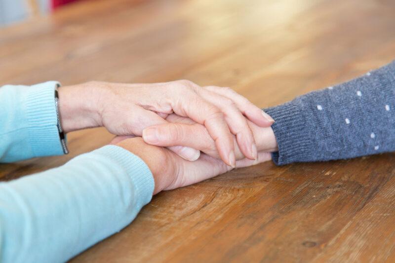 Mãos de uma pessoa sobre a mão de outra pessoa como forma de consolação