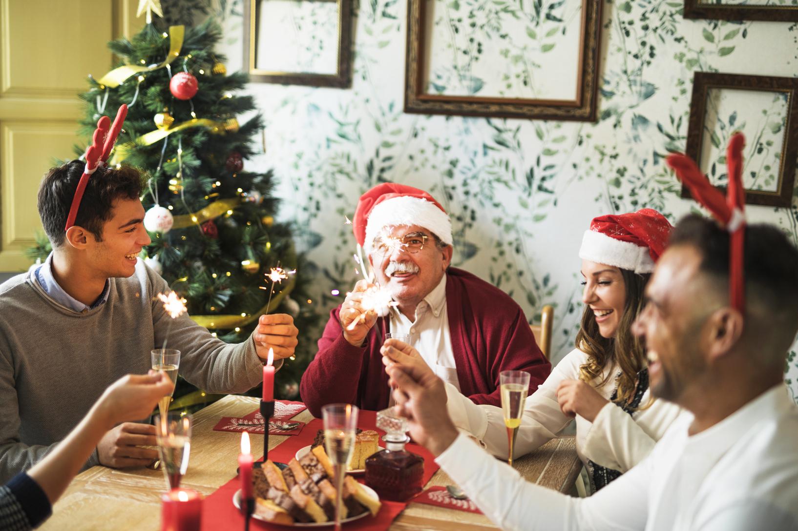 família sentada junto à mesa para a ceia de Natal